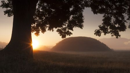 Sunset over the famous burial mounds, shrouded by mist, at Sutton Hoo. Suffolk Picture: NATIONAL TRU