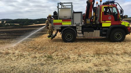 The crew of the Unimog damping down the field fire at Stanningfield. Picture: RUSSELL COOK