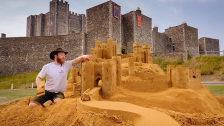 Sand sculptor Jamie Wardley puts the finishing touches to English Heritage's ultimate sandcastle at