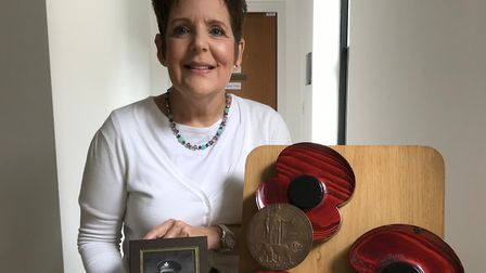 Jan Bloomfield with three of the wooden poppies, a penny cast in memory of her great great uncle Pte