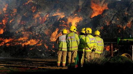 Firefighters tackle a straw stack fire in Horsford, Norfolk Picture: ADRIAN JUDD