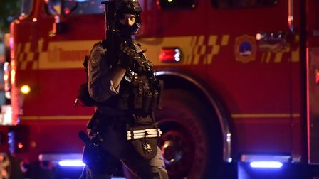 A tactical officer works the scene of a shooting in Toronto Picture: FRANK GUNN/THE CANADIAN PRESS v