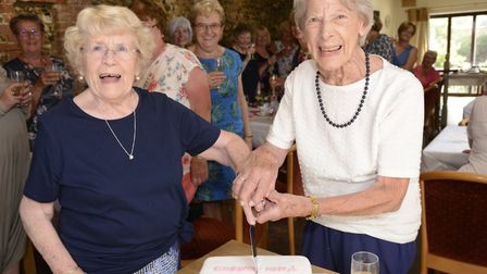 Myra Clelland and Marie Bass cut the cake to mark the milestone of the Mother's Group at Greene King