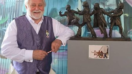 Tom Murray with the mini bronze statue of his image. A full size version may be placed in central Lo