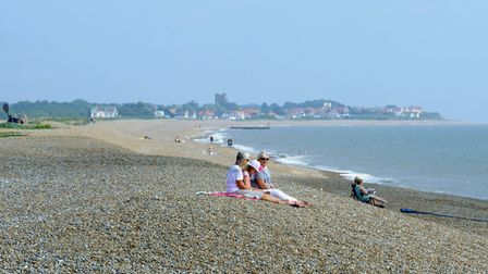 Lazy days: Warm early morning sunshine for weekend visitors to Aldeburgh beach looking towards the S