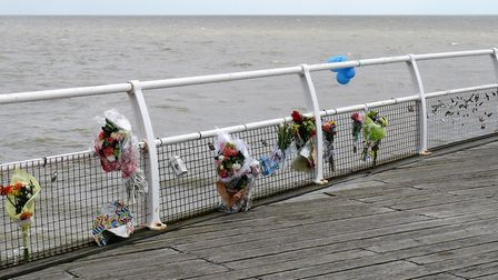 Floral tributes to 15-year-old Ben Quartermaine line railings at Clacton Pier Picture: NIGEL BROWN