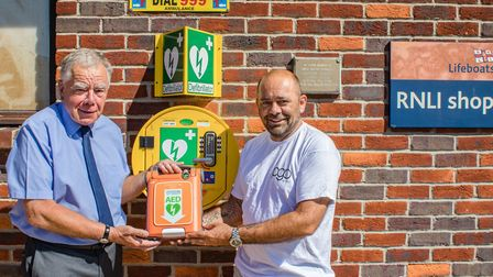 Bruce Oxley, a director of PG Oxley, hands over the defibrillator unit to Philip Oxley, chairman of