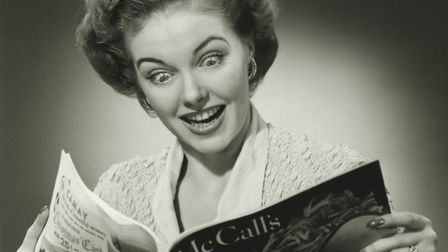 Woman looking surprised, reading fashion magazine (B&W), (Close-up) Picture: George Marks