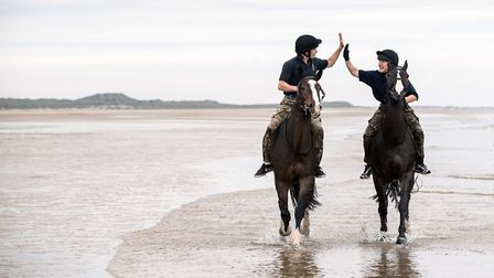Soldiers from The King's Troop Royal Horse Artillery hi-5 while riding in the sea at Holkham beach.