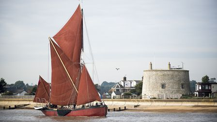 A Thames barge entering the River Deben at Felixstowe Ferry as it passes one of the Martello Towers