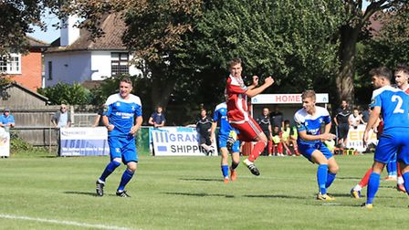Miles Powell (second right) drives the the ball through a crowded Bury penalty area to double the sc