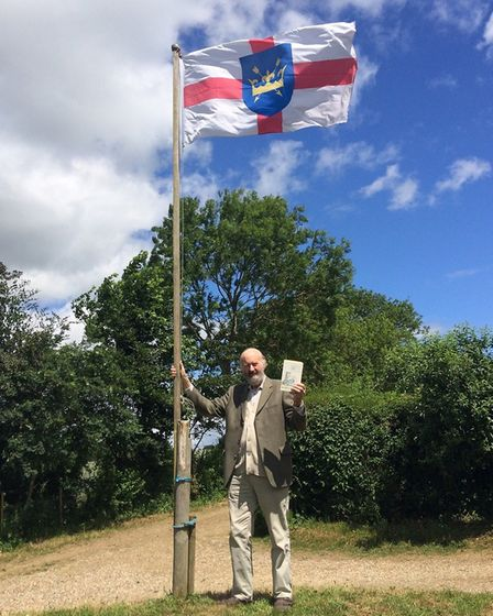 Author John Rogers hoists the Suffolk flag at his Rendham home on Suffolk Day Picture: SUPPLIED BY F