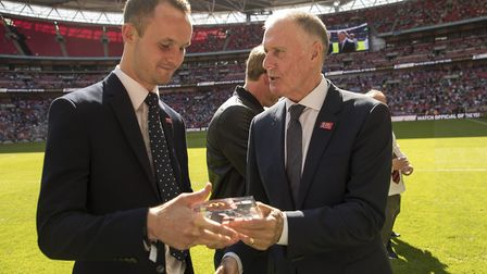 George Byrne (left) receives his Match Official of the Year award on the Wembley pitch from former E