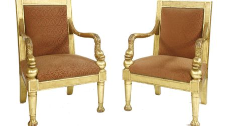 A pair of gilt armchairs with dolphin arms from Rod Stewart's colelction. Picture: Sworders