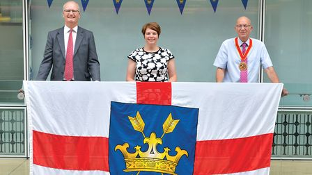 Suffolk County Council's Matthew Hicks, Nicola Beach and Michael Ladd with the St Edmunds Flag Pictu
