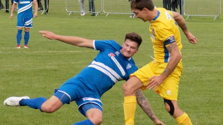 Brantham's George Clarke (blue) is about to tackle Spalding captain Ben Davison during the Suffolk s