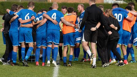 Brantham players and staff in a celebratory huddle following their 1-0 win over Spalding United. Pic