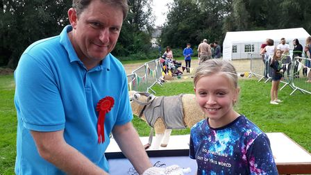Alice Selwood won the children's sheep throwing and gets her cuddly sheep prize from fete chairman A