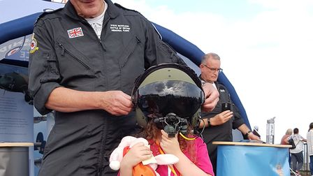 A young girl tries on a pilot's helmet at the Clacton Airshow. Picture: RACHEL EDGE