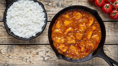 Traditional chicken tikka masala Indian spicy meat food with rice in cast iron skillet on vintage wo