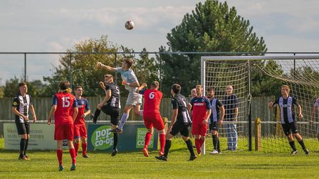Woodbridge 'keeper Alfie Stronge punches clear against Hadleigh in the FA Cup last weekend. Photo: P