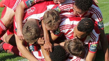 The whole Felixstowe team join in the celebrations with Sam Ford buried beneath after his late secon