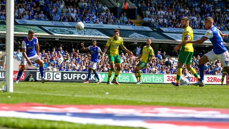 Gwion Edwards (on ground between legs of Grant Hanley) watches as his shot heads towards the back of