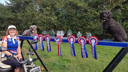 Mrs Thomson poses alongside her haul of rosettes and trophies collected from the ParAgility world Ch
