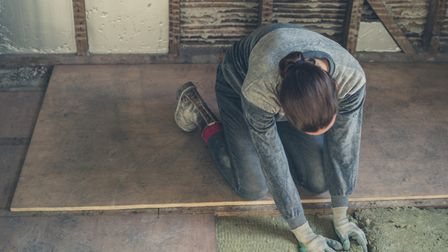 Keep it warm: A woman laying floor insulation in the loft. Picture: Thinkstock/PA.