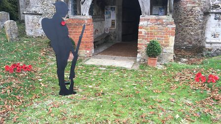 The life sized model of a World War One soldier alongside some of the hand made poppies at Stradisha