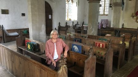 Jane Helliwell in Stradishall Church with the life-sized sitting silhouettes. Picture: RUSSELL COOK