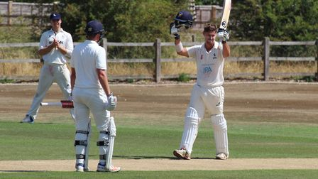 Kyran Young holds his arms aloft to celebrate his maiden century for Suffolk against Hertfordshire a