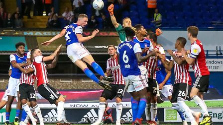 Matthew Pennington looks to head for goal as Brentford keeper Daniel Bentley punches clear. Photo: S
