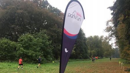 The distinctive parkrun banner, with runners in the background taking part in Saturday's Bury St Edm
