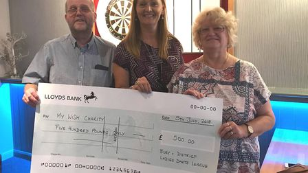 Tony Fayers, the chairman of the Bury and District Ladies Darts League, and Sue Aris, right, hand ov
