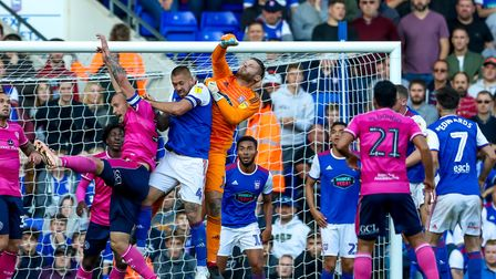 Town keeper Dean Gerken punches a QPR corner clear, with captains Luke Chambers and Toni Leistner al