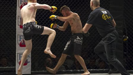Ollie Sarwa, left, launches the fight-ending assault on John Parthaugen to win the Cage Warriors Aca