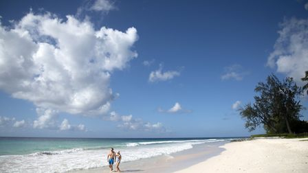 Couple hand in hand walking on the shoreline of Caribbean beach Picture: FRED. OLSEN CRUISE