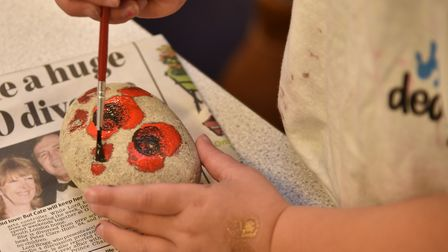 Children from Fairfield Infant School join the mayor Graham Newman in painting stones with poppies f
