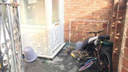 Remnants of burned belongings of the family believed to live in the flat are outside the front door.