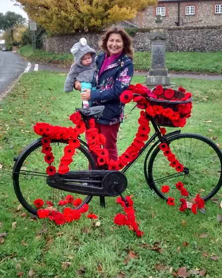 Caroline Dowson and granddaughter Florence with the bicycle decorated with knitted poppies in Barnha