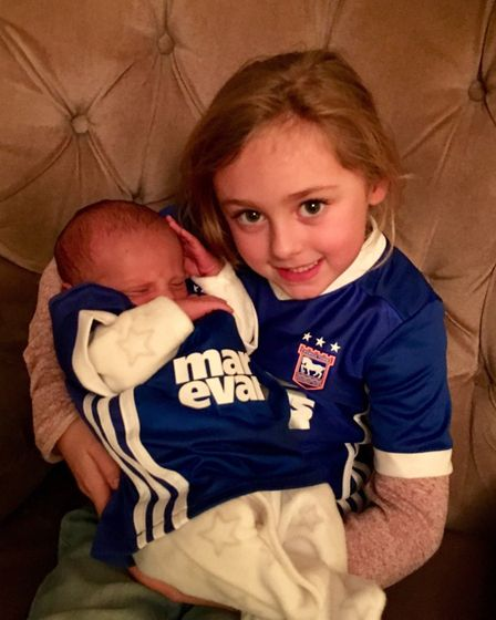 14-day-old Michael sits with his Ipswich mad sister Francesca, 5 Picture: KRIS CAPELING