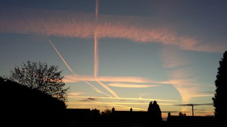 The sky over Boxford at sunset, criss-crossed with aircraft vapour trails, at 18.01 BST on 21 Octobe