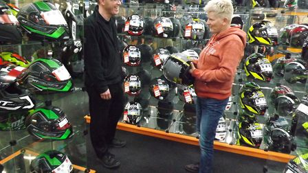 Parts, clothing and accessories advisor Dan Williams helps customer Janine Norris buy a new crash he