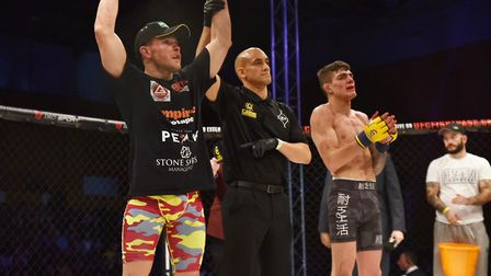 Steve Aimable, left, has his hand raised after his win over Josh Abraham at Cage Warriors 99 in Colc