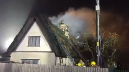 Fire fighter could be seen fighting the blaze on top of the house. Picture: ANDY THOMPSON