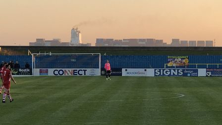 A container ship heads down the Thames and behind the Canvey Island ground, as Sudbury took the poin