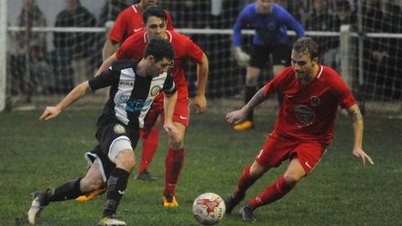 Action from Saturday's goalless draw at Swaffham Town, as home captain Alex Vincent tries to make pr