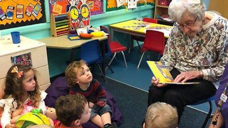 Olwyn Hopkins, a resident of Davers Court Care Home, in Bury St Edmunds, reading to youngsters at th