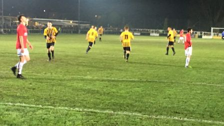 Stowmarket players (yellow and black) celebrate their first-half equaliser against Swaffham. Picture